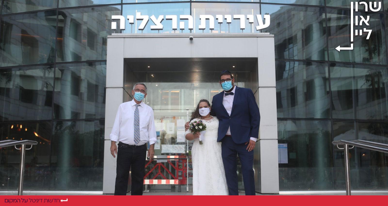 משה פדלון וזוג מתחתנים בפתח בניין עיריית הרצליה