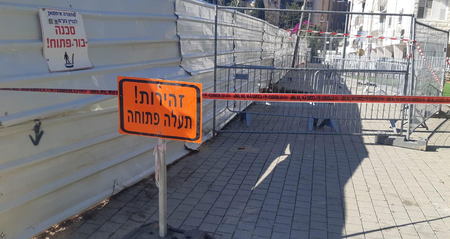שלט זהירות! תעלה פתוח - סמוך לבור שנפער ליד אתר בניה ברחוב האודם